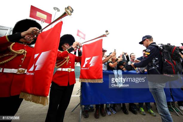 Max Verstappen of Netherlands and Red Bull Racing signs autographs for fans as Queens Guards wearing traditional bearskin hats play horns at the...
