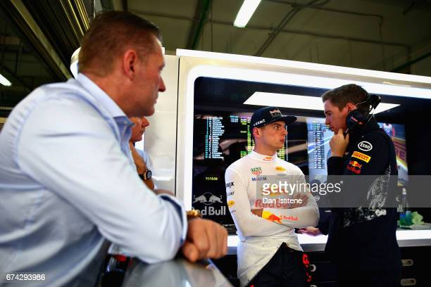 Max Verstappen of Netherlands and Red Bull Racing talks with a Red Bull Racing team member as his father Jos Verstappen looks on during practice for...
