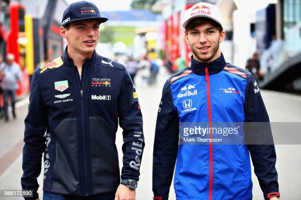 Max Verstappen of Netherlands and Red Bull Racing talks with Pierre Gasly of France and Scuderia Toro Rosso in the Paddock during previews ahead of...