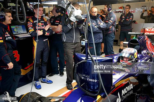 Max Verstappen of Netherlands and Scuderia Toro Rosso watches as his father Jos Verstappen sits in his car in the garage after qualifying was...