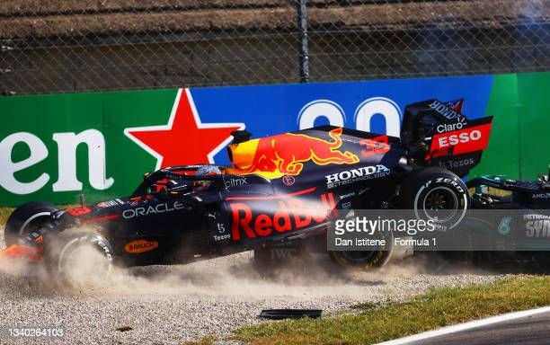 Max Verstappen of the Netherlands and Red Bull Racing and Lewis Hamilton of Great Britain and Mercedes AMG Petronas collide at the first chicane and...