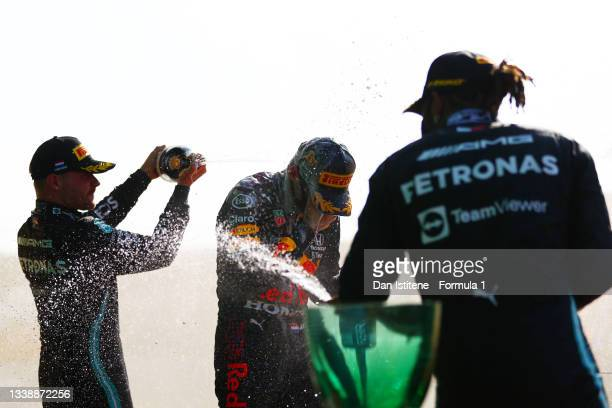 Max Verstappen of the Netherlands and Red Bull Racing celebrates victory on the podium with Lewis Hamilton of Great Britain and Mercedes AMG Petronas...