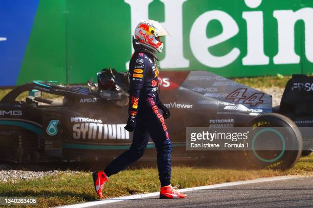 Max Verstappen of the Netherlands and Red Bull Racing walks past the Lewis Hamilton of Great Britain and Mercedes AMG Petronas after they collided at...