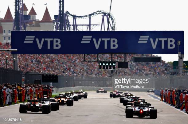 Max Verstappen of the Netherlands driving the Aston Martin Red Bull Racing RB14 TAG Heuer and Brendon Hartley of New Zealand driving the Scuderia...