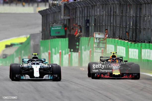 Max Verstappen of the Netherlands driving the Aston Martin Red Bull Racing RB14 TAG Heuer overtakes Valtteri Bottas driving the Mercedes AMG Petronas...