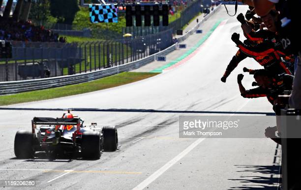 Max Verstappen of the Netherlands driving the Aston Martin Red Bull Racing RB15 crosses the line to take the chequered flag and the win as the Red...
