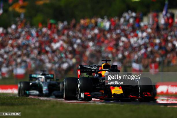Max Verstappen of the Netherlands driving the Aston Martin Red Bull Racing RB15 leads Lewis Hamilton of Great Britain driving the Mercedes AMG...