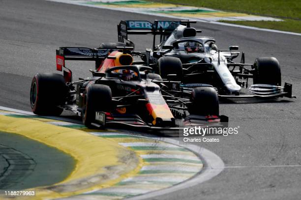 Max Verstappen of the Netherlands driving the Aston Martin Red Bull Racing RB15 overtakes Lewis Hamilton of Great Britain driving the Mercedes AMG...