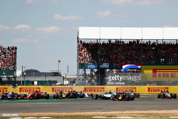 Max Verstappen of the Netherlands driving the Aston Martin Red Bull Racing RB14 TAG Heuer runs wide as Lewis Hamilton of Great Britain driving the...