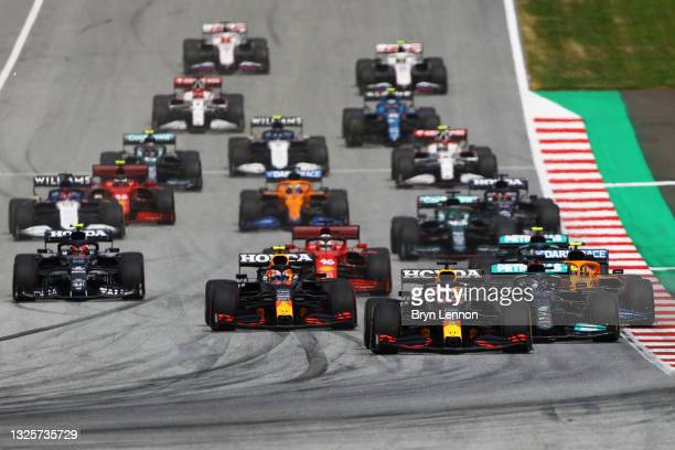 Max Verstappen of the Netherlands driving the Red Bull Racing RB16B Honda leads the field into turn one at the start during the F1 Grand Prix of...