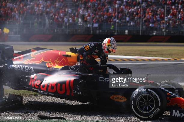 Max Verstappen of the Netherlands driving the Red Bull Racing RB16B Honda climbs from his car after crashing during the F1 Grand Prix of Italy at...