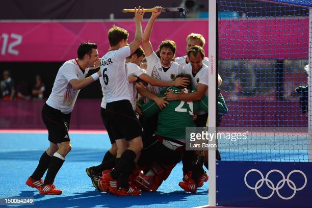 Max Weinhold of Germany and his team mates celebrate victory at the end of the Men's Hockey Semi Final match between Australia and Germany on Day 13...