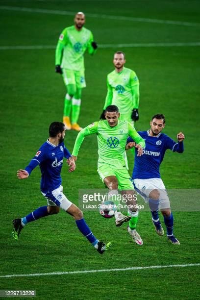 Maxence Lacroix of Wolfsburg in action against Ahmet Kutucu of Schalke and Nabil Bentaleb of Schalke during the Bundesliga match between FC Schalke...
