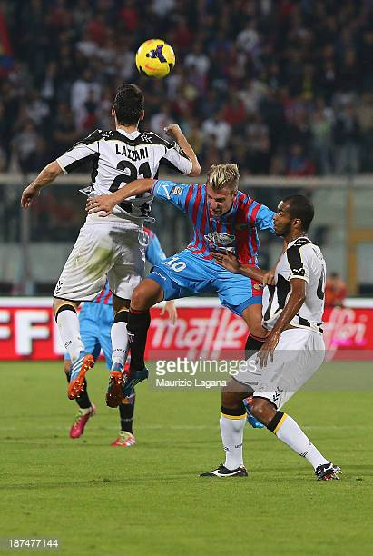 Maxi Lopez of Catania competes for the ball in air with Andrea Lazzari and Edinaldo Gomes Pereira of Udinese during the Serie A match between Calcio...