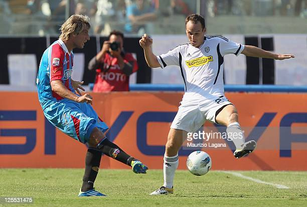 Maxi Lopez of Catania competes for the ball with Steve von Bergen of Cesena during the Serie A match between Catania Calcio and AC Cesena at Stadio...