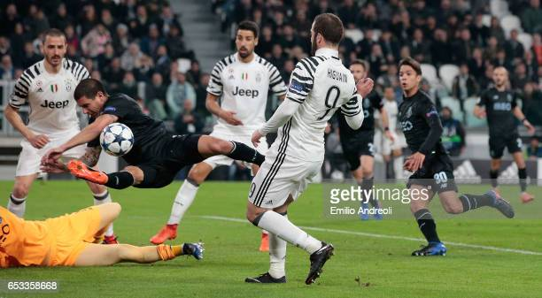 Maxi Pereira of FC Porto C appears to handle the ball in the penalty area as Gonzalo Higuain shoots towards goal during the UEFA Champions League...