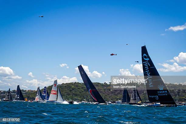 Maxi racing yachts and TV helicopters pictured following the start of the Rolex Sydney Hobart Yacht Race with the firing of a starting cannon at...