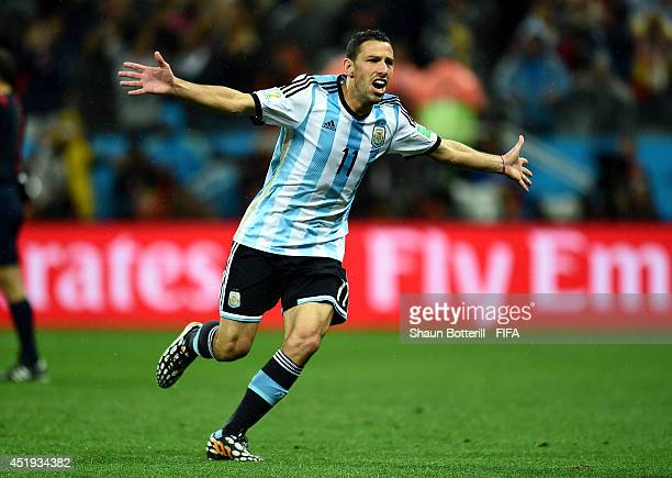 Maxi Rodriguez of Argentina celebrates after scoring a penalty in the penalty shootout to win the 2014 FIFA World Cup Brazil Semi Final match between...