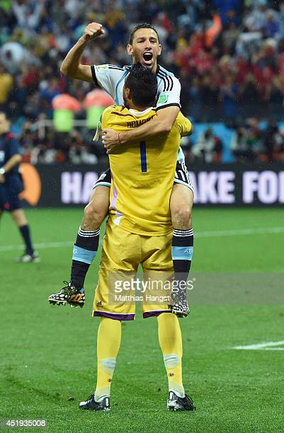 Maxi Rodriguez of Argentina celebrates with goalkeeper Sergio Romero after making his penalty kick to defeat the Netherlands in a shootout during the...