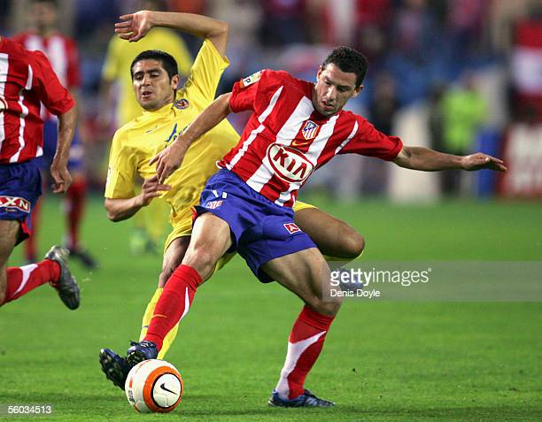 Maxi Rodriguez of Atletico Madrid tackles Roman Riquelme of Villarreal during a Primera Liga match between Atletico Madrid and Villarreal at the...