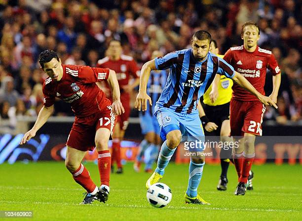 Maxi Rodriguez of Liverpool challenges Burak Yilmaz of Trabzonspor AS during the UEFA Europa League Play off first leg Qualifying match between...