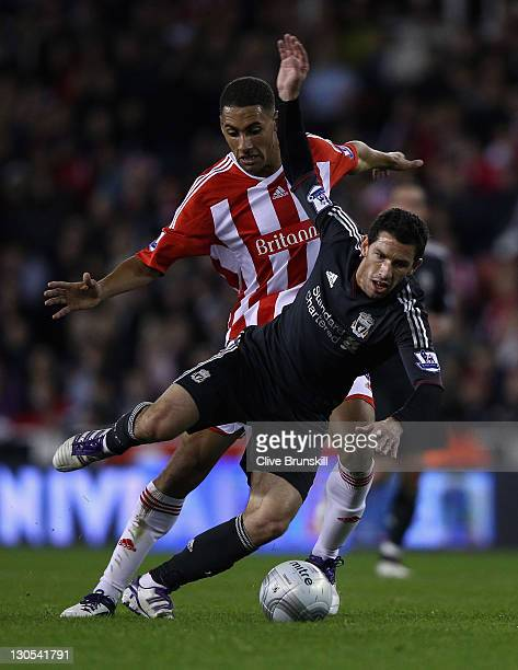 Maxi Rodririguez of Liverpool is tackled by Ryan Shotton of Stoke City during the Carling Cup Fourth Round match between Stoke City and Liverpool at...