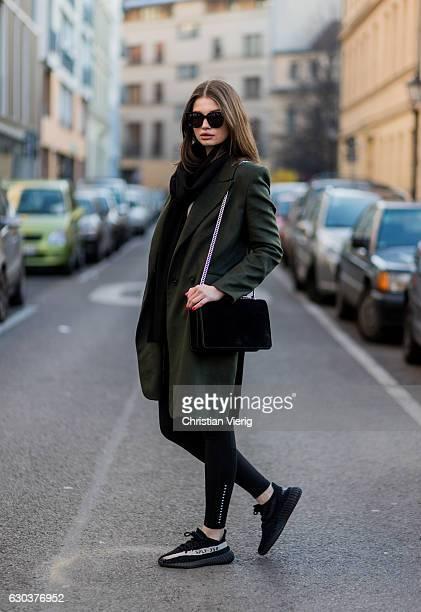 Maxilie Mlinarskij is wearing a green Dawid Tomaszewski wool coat a black Agneel bag black HM leggings Gentle Monster sunglasses black Adidas yeezy...