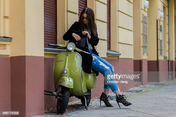 Maxilie Mlinarskij on a old Vespa checking her bag wearing a blue ripped denim jeans from Zara a black vintage coat a black Chanel bag a grey shirt...