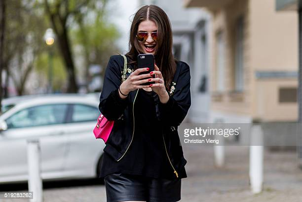 Maxilie Mlinarskij on the phone snapchatting and seen wearing a black bomber jacket from Zara black leather shorts from Zara a pink bag from...
