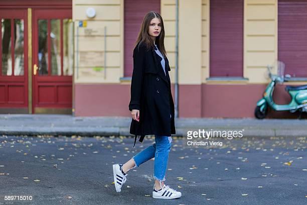 Maxilie Mlinarskij wearing a blue ripped denim jeans from Zara a black vintage coat a grey shirt from Alexander Wang white Adidas Superstar sneaker...