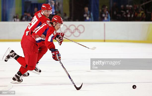Maxim Afinogenov and Alexei Yashin of Russia pursue the puck during the second period of the men's ice hockey Preliminary Round Group B match against...