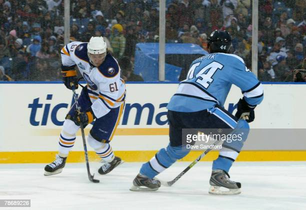 Maxim Afinogenov of the Buffalo Sabres controls the puck against Brooks Orpik of the Pittsburgh Penguins in the NHL Winter Classic at the Ralph...