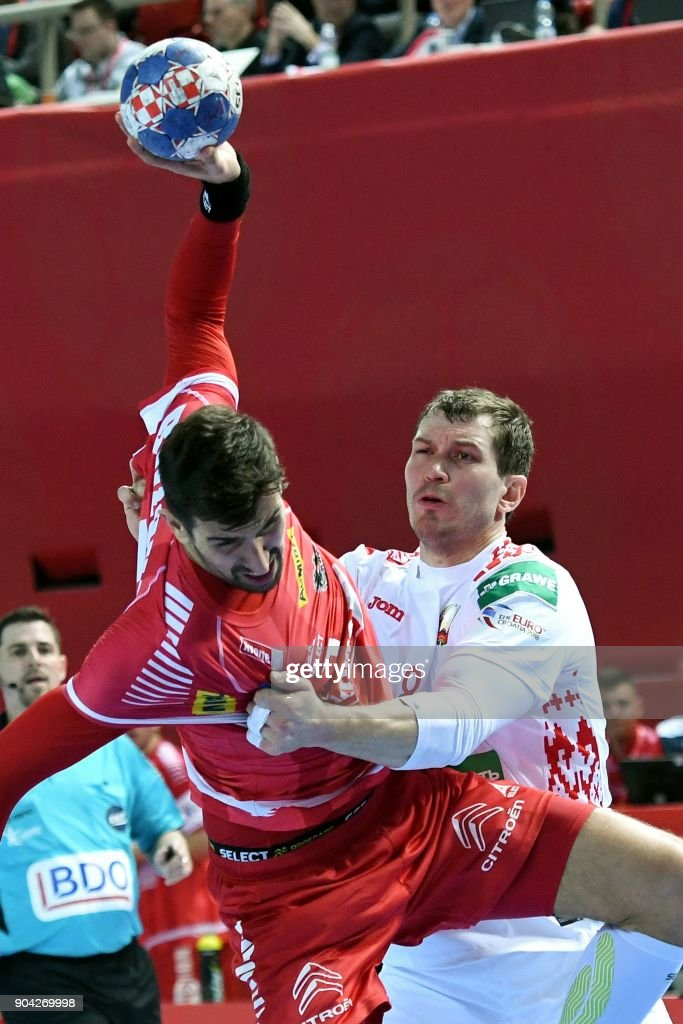Maxim Babichev (R) of Belarus vies for the ball with Janko Bozovic of Austria during the preliminary round group B match of the Men's 2018 EHF European Handball Championship between Belarus and Austria in Porec, Croatia on January 12, 2018. /