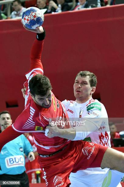 Maxim Babichev of Belarus vies for the ball with Janko Bozovic of Austria during the preliminary round group B match of the Men's 2018 EHF European...