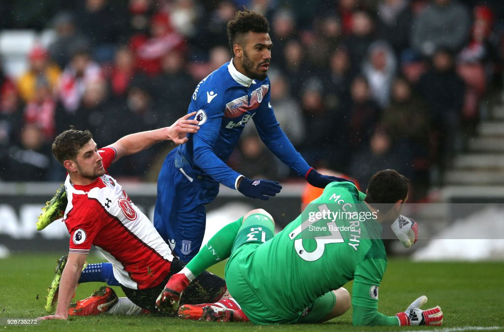 Maxim Choupo-Moting of Stoke City goes down as he is tackled by Jack Stephens and Alex McCarthy of Southampton during the Premier League match between Southampton and Stoke City at St Mary's Stadium on March 3, 2018 in Southampton, England.