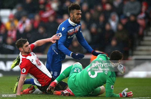 Maxim ChoupoMoting of Stoke City goes down as he is tackled by Jack Stephens and Alex McCarthy of Southampton during the Premier League match between...