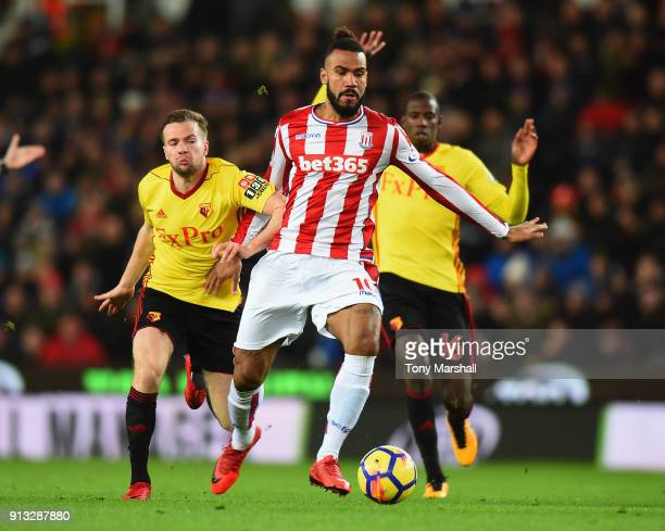 Maxim ChoupoMoting of Stoke City is tackled by Tom Cleverly of Watford during the Premier League match between Stoke City and Watford at Bet365...