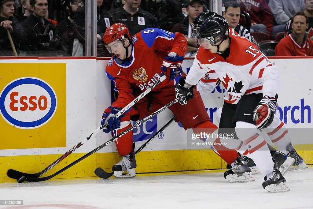Maxim Goncharov #5 of Team Russia and Stefan Della Rovere #15 of Team Canada battle for the puck during the game at the semifinals at the IIHF World Junior Championships at Scotiabank Place on January 03, 2009 in Ottawa, Ontario, Canada.