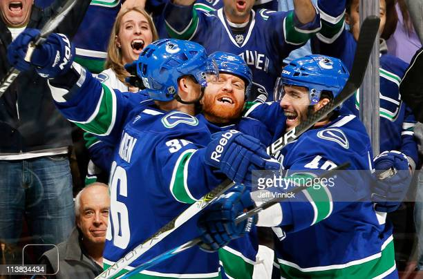 Maxim Lapierre and Jannik Hansen of the Vancouver Canucks celebrate goal by Raffi Torres against the Nashville Predators during Game Five of the...