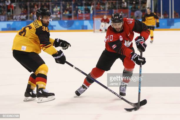 Maxim Lapierre of Canada controls the puck against Yannic Seidenberg of Germany during the Men's Playoffs Semifinals on day fourteen of the...