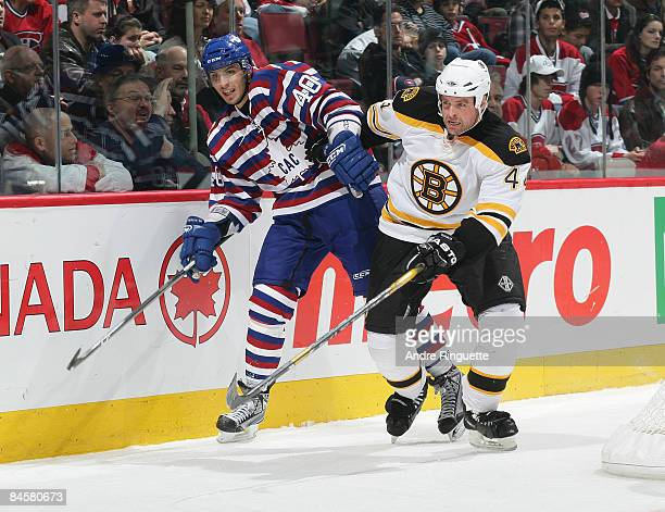 Maxim Lapierre of the Montreal Canadiens battles along the boards against Aaron Ward of the Boston Bruins at the Bell Centre on February 1 2009 in...