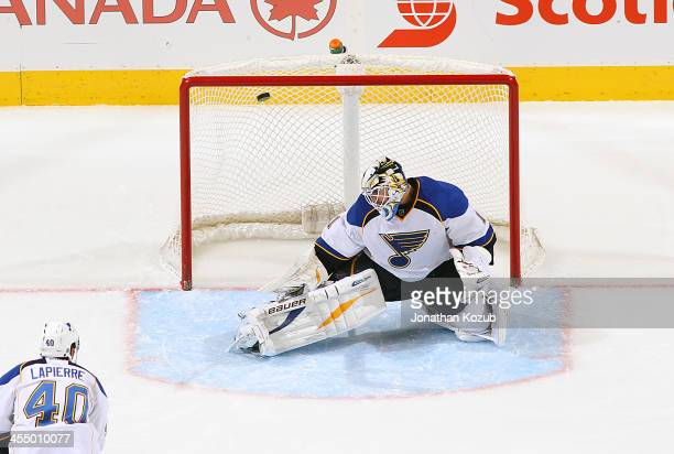 Maxim Lapierre of the St Louis Blues watches as the puck goes over the shoulder of teammate Brian Elliott on a shot by Bryan Little of the Winnipeg...