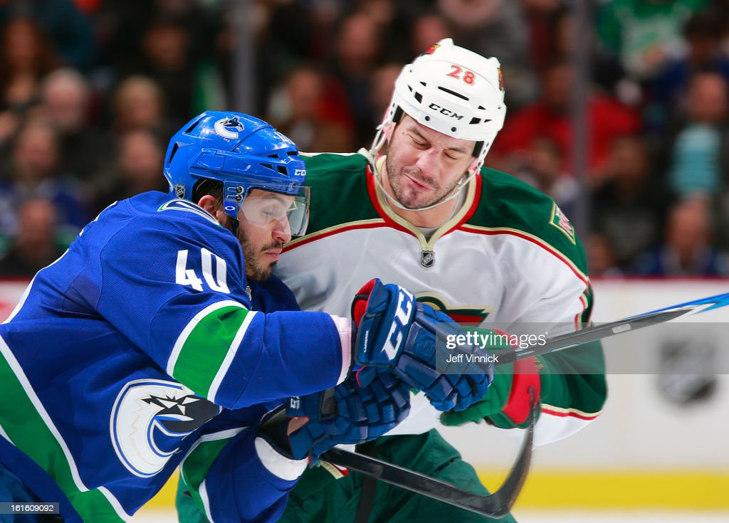 Maxim Lapierre #40 of the Vancouver Canucks and Zenon Konopka #28 of the Minnesota Wild collide during their NHL game at Rogers Arena February 12, 2013 in Vancouver, British Columbia, Canada.