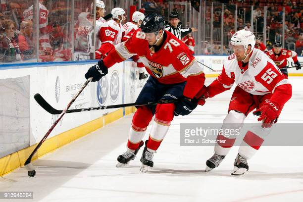 Maxim Mamin of the Florida Panthers digs the puck out from the boards against Niklas Kronwall of the Detroit Red Wings at the BBT Center on February...