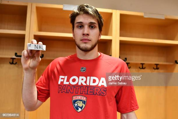 Maxim Mamin of the Florida Panthers poses in the locker room with a puck after playing his first NHL game against the Columbus Blue Jackets on...