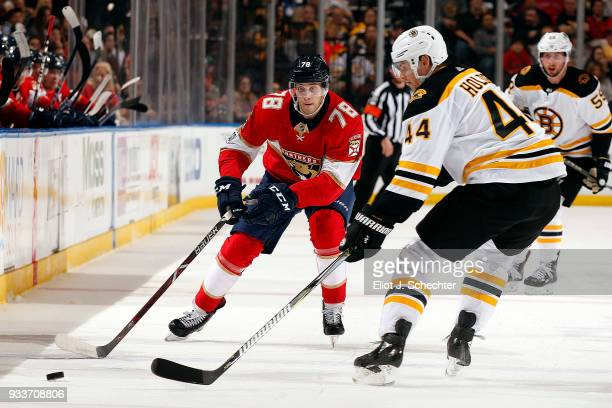 Maxim Mamin of the Florida Panthers skates for possession against Nick Holden of the Boston Bruins at the BBT Center on March 15 2018 in Sunrise...