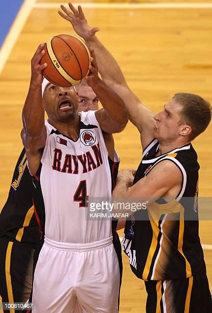 Maxim Voyeikov and Alexandr Tyutyunik of Kazakhstan's Astana Tigers challenge Cory Dion Bradford of Qatar's Al-Rayyan during their 21st FIBA Asia...