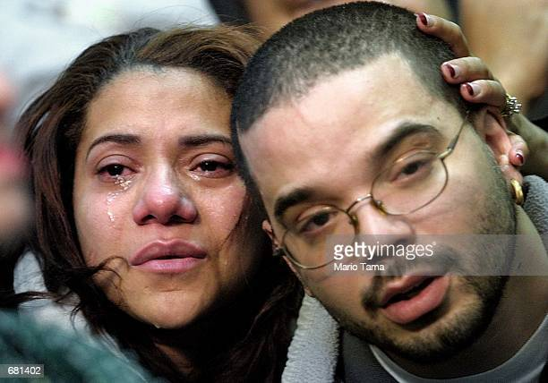 Maxima Nunez and Carlos Morales grieve at a service for family members of the victims of the American Airlines Flight 587 crash November 12 2001 in...