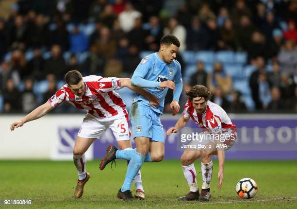 Maxime Biamou of Coventry City is challenged by Kevin Wimmer and Joe Allen of Stoke City during The Emirates FA Cup Third match between Coventry City...