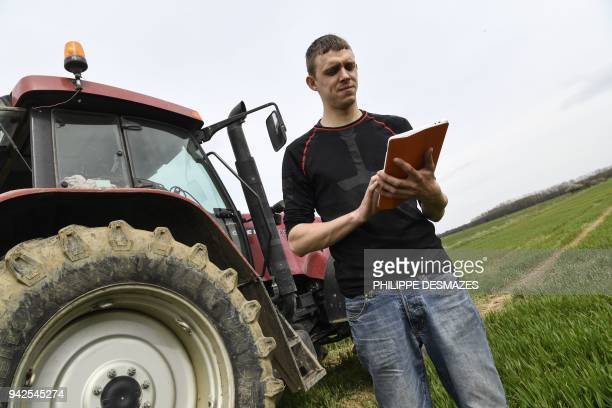 Maxime Carre a young farmer uses his tablet connected to a highspeed radio internet network before working in the fields on April 3 in...